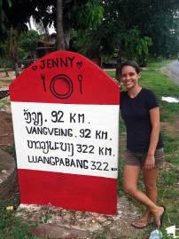 Tara next to a distance marker in Laos